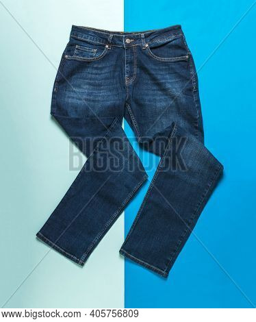 Fancifully Folded Men's Jeans On A Light And Dark Blue Background. Jeans And Denim Wear.