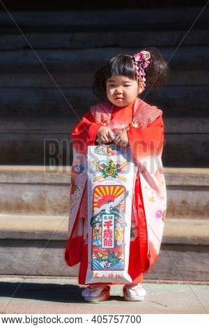Kanazawa, Japan - November 15, 2018: Japanese girl with gift posing during Shichi-Go-San day at Oyama Jinja Shrine. Shichi-Go-Sun is annual festival day in Japan for 3, 5 and 7 years old children.