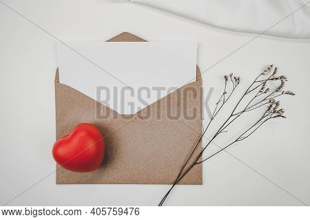 Blank White Paper Is Placed On Open Brown Paper Envelope With Red Heart And Limonium Dry Flower And