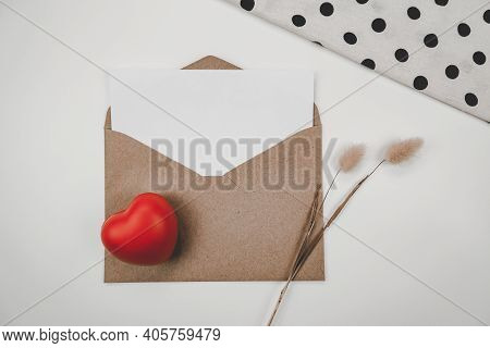 Blank White Paper Is Placed On Open Brown Paper Envelope With Red Heart And Rabbit Tail Dry Flower A