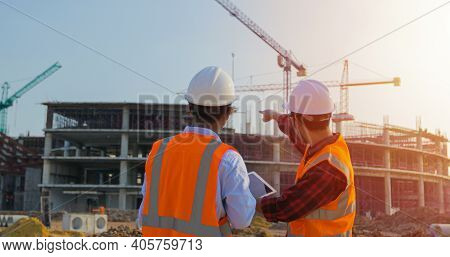 Two Asian Engineering Using The Tablet For Discussion And Working At Construction On Site