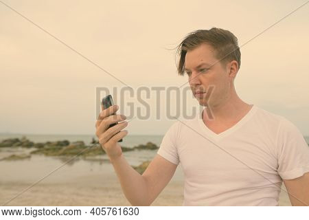 Young Handsome Man Using Mobile Phone At The Public Beach Of Hua Hin In Thailand