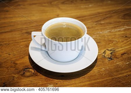 Hot Coffee In A White Cup On A Wooden Table