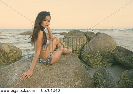 Young Beautiful Asian Woman Sitting And Posing On The Rocks Of Public Beach In Hua Hin Thailand