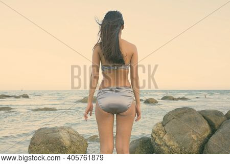 Back View Of Young Beautiful Asian Woman Standing On The Rocks Of Public Beach In Hua Hin Thailand