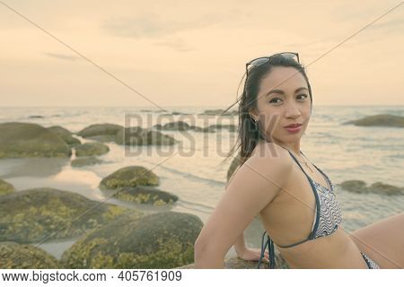 Young Beautiful Asian Woman Thinking While Sitting On The Rocks Of Public Beach In Hua Hin Thailand
