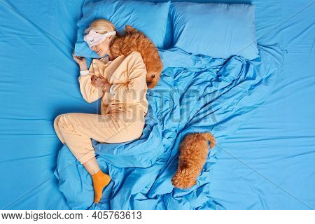 Relaxed Blonde Adult Woman Wears Blindfold On Eyes Sleeps Well In Bed Wears Comfortable Pajama Two F