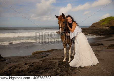Smiling Woman Leading Horse By Its Reins. Cuddling Horse. Love To Animals. Asian Woman Wearing Long
