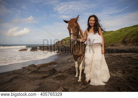 Happy Woman Leading Horse By Its Reins. Horse Riding On The Beach. Human And Animals Relationship. A