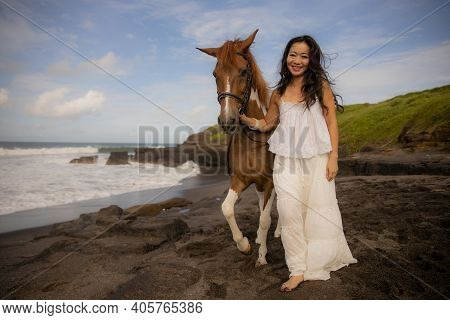 Smiling Woman Leading Horse By Its Reins. Horse Riding On The Beach. Human And Animals Relationship.