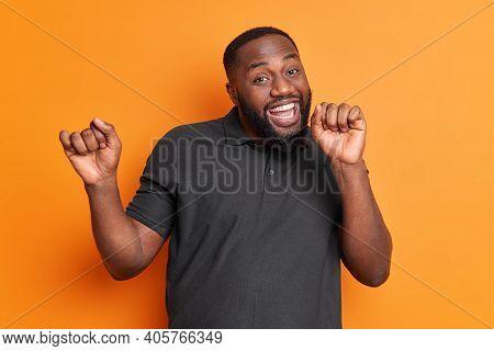 Studio Shot Of Carefree Positive Black Man With Thick Beard Dances Carefree Has Upbeat Mood Raises A