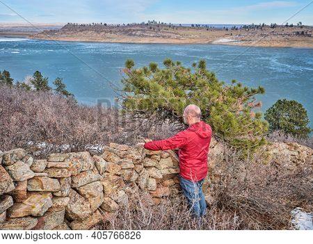 senior hiker at old stone fence overlooking frozen mountain lake  - Horsetooth Reservoir at foothills of Rocky Mountains - a popular recreational area in northern Colorado, fall or winter scenery