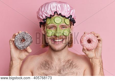Portrait Of Cheerful Young Man Applies Green Nourishing Mask With Cucumber Slices Holds Two Glazed D