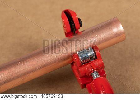 Cutting A Copper Pipe With A Red Pipe Cutter
