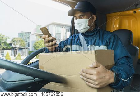 Young Asian Men Wearing Protective Mask While Working. Delivery Man And Parcel Box With Smartphone I
