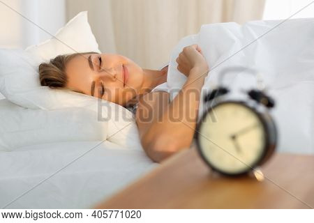 Beautiful Young Woman Sleeping While Lying In Bed Comfortably And Blissfully Sunbeam Dawn On Her Fac
