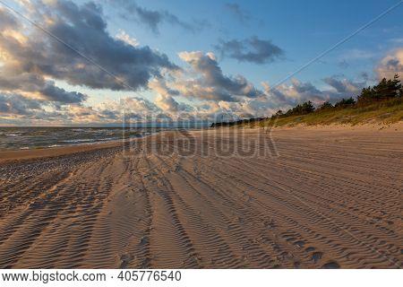 Wild Sandy Beach Under Cloudy Sky Of Sunset