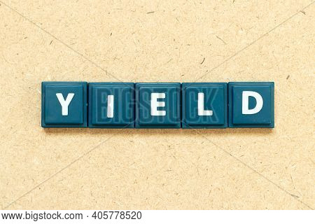Tile Alphabet Letter In Word Yield On Wood Background