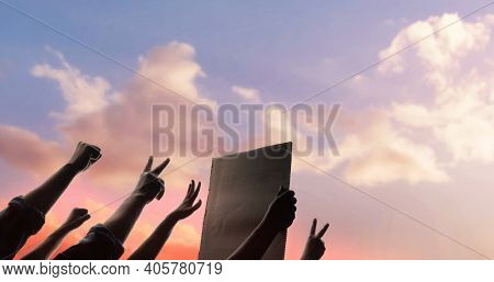 Protest, Mob, Expression And Strike Concept.  Silhouette Of People Raise Up Hands Into The Sky. The