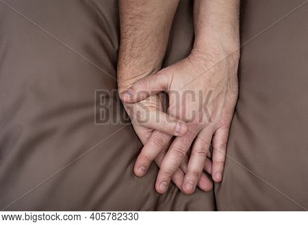 Lgbt Concept. Men Holding Hands On The Bed