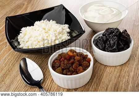 Black Glass Bowl With Defatted Grainy Cottage Cheese, Bowl With Sour Cream, Spoon, Bowls With Raisin