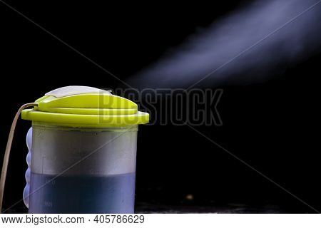 Picture Of A Steam Coming Out Of The Hole Of A Hot Water Steamer On Pitch Black Background. Steamer