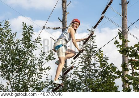 A 30-35-year-old Woman In Climbing Gear Climbs Up A Rope Ladder, Looks At The Camera. Concept: Sport