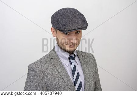 Portrait Of A 35-year-old Man With A Beard In A Suit And Cap On A Gray Background, Selective Focus 2