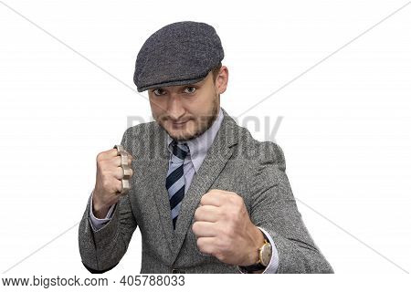 Portrait Of A Man In A Boxing Stance With Brass Knuckles In His Hand On A White Background.the Conce