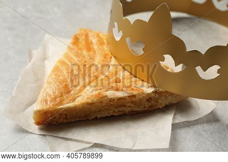 Slice Of Traditional Galette Des Rois With Paper Crown On Light Grey Table, Closeup