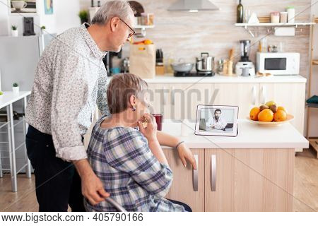 Senior People Using Medical App On Tablet To Talk With Doctor About Her Pills Prescription Online He