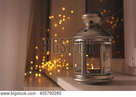 Decorative Christmas Lantern With Burning Candle On Windowsill. Space For Text