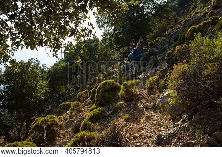 Hiking Lycian way. Man is trekking on steep slope stony path, on mountain on Mediterranean coast, evening warm light on bushes, Outdoor activity in Turkey