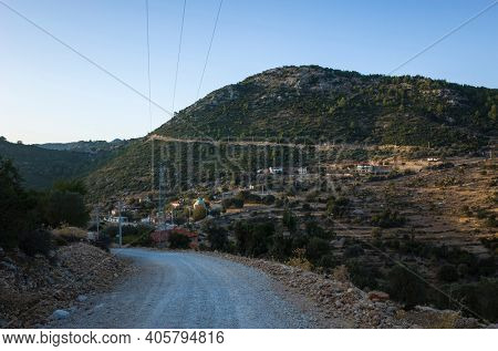 Small remote village Gey in mountains of Mediterranean region in Turkey, View from Lycian way hiking trail, Evening last light, gravel road
