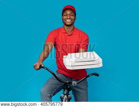 Best Fast Food Delivery. Portrait Of Smiling African Courier Wearing Red Cap And Uniform Holding Piz