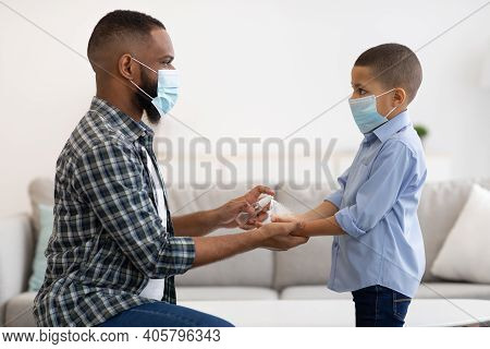 Covid-19 Prevention. Black Father Using Sanitizer With His Son Applying Spray Cleaning His Kids Hand