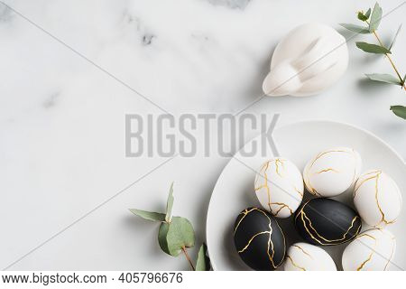 Elegant Easter Flat Lay Composition. Black And Golden Easter Eggs, Rabbit Bunny, Eucalyptus Leaves O