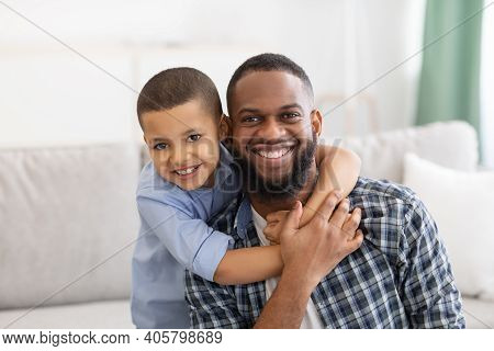 Portrait Of Cheerful African Father And Son Hugging Posing Smiling To Camera Sitting On Couch At Hom