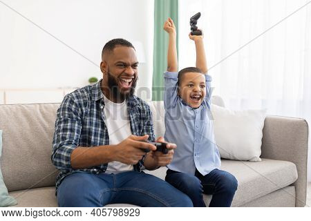 Joyful African Daddy And His Son Winning Video Game Celebrating Victory Together Sitting On Sofa Ind