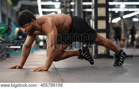 Plank Work Out Concept. Active Shirtless Black Man Making Work Out On Floor In Modern Male Gym, Side