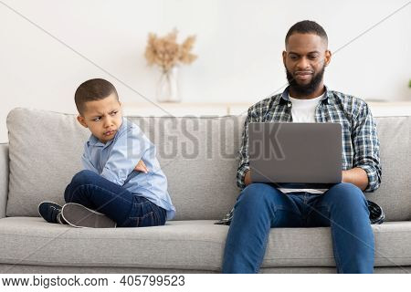 Indifferent African Father Using Laptop Ignoring Offended Son Sitting On Sofa At Home. Family Proble