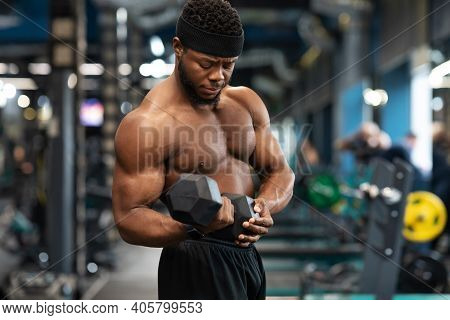 Biceps Workout Session. Concentrated African American Shirtless Athlete Training Arms With Dumbbells