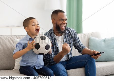 Happy African American Father And Son Watching Sports On Tv Holding Soccer Ball And Remote Control S