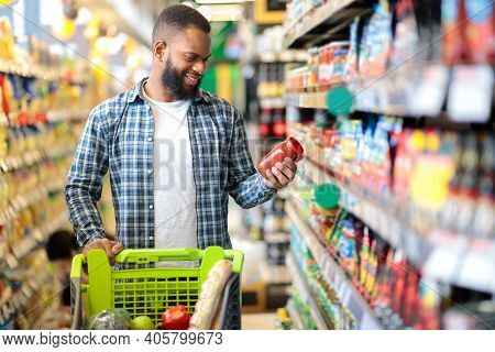 Customer In Supermarket. Black Man Doing Grocery Shopping Standing With Cart Choosing Food Product I