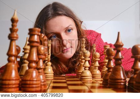 Adult Woman Playing Chess While Sitting On The Bed At The Chessboard, Face Close Up