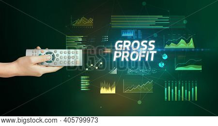 hand holding wireless peripheral with GROSS PROFIT inscription, cyber business concept
