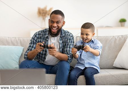 Joyful Black Dad And Son Play Videogame Together Having Fun On Weekend Sitting On Sofa At Home. Youn
