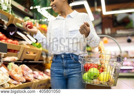 African American Woman Doing Grocery Shopping In Supermarket. Cropped, Selective Focus On Basket Ful