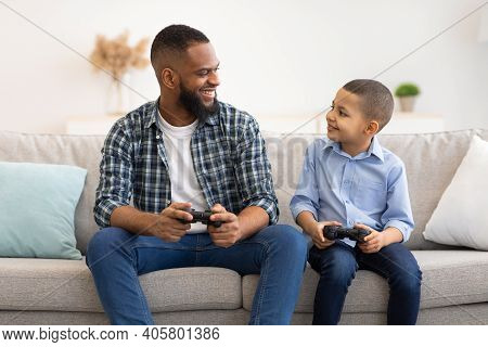 Happy Black Daddy And His Kid Son Playing Video Games Smiling Each Other Sitting With Game Controlle