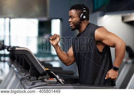 Jogging Workout. Joyful Black Man In Modern Wireless Headphones Running On Treadmill At Gym, Looking